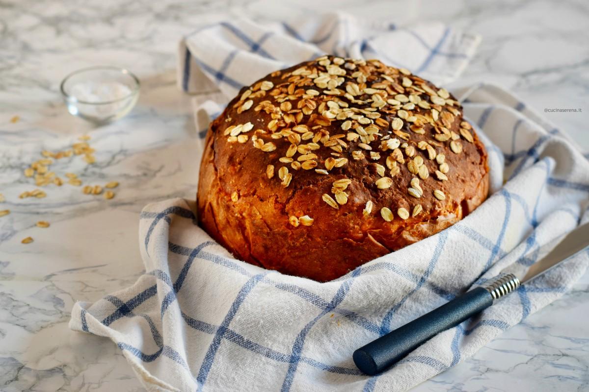 soda bread nella foto avvolto in un canovaccio bianco con righe a quadri blu, il pane è ricoperto di fiocchi di avena sullo sfondo si vede il bicarbonato e i fiocchi di avena