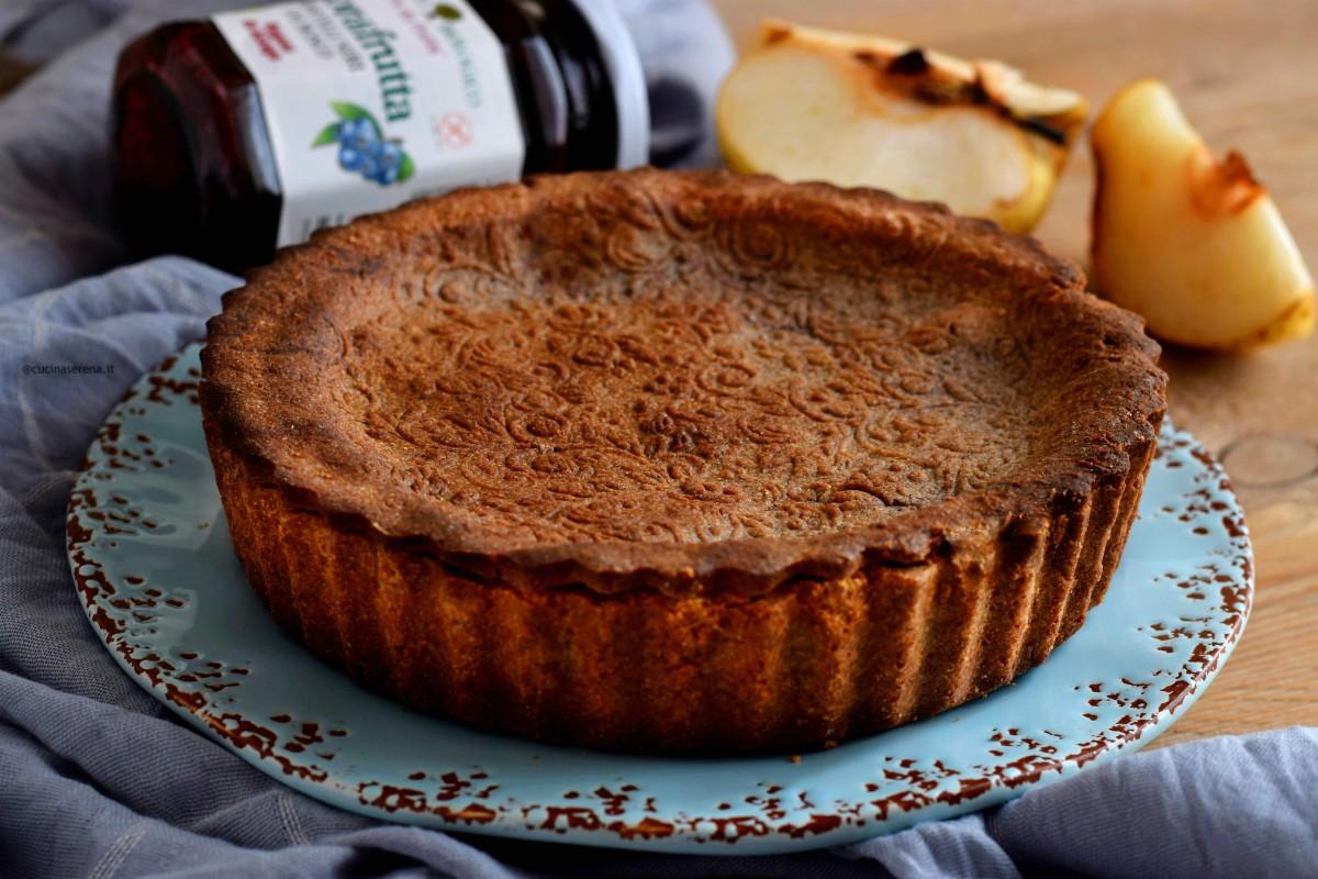 Crostata grano saraceno con pere nashi e confettura di mirtilli neri di bosco, nella foto presentata intera in un piatto celeste