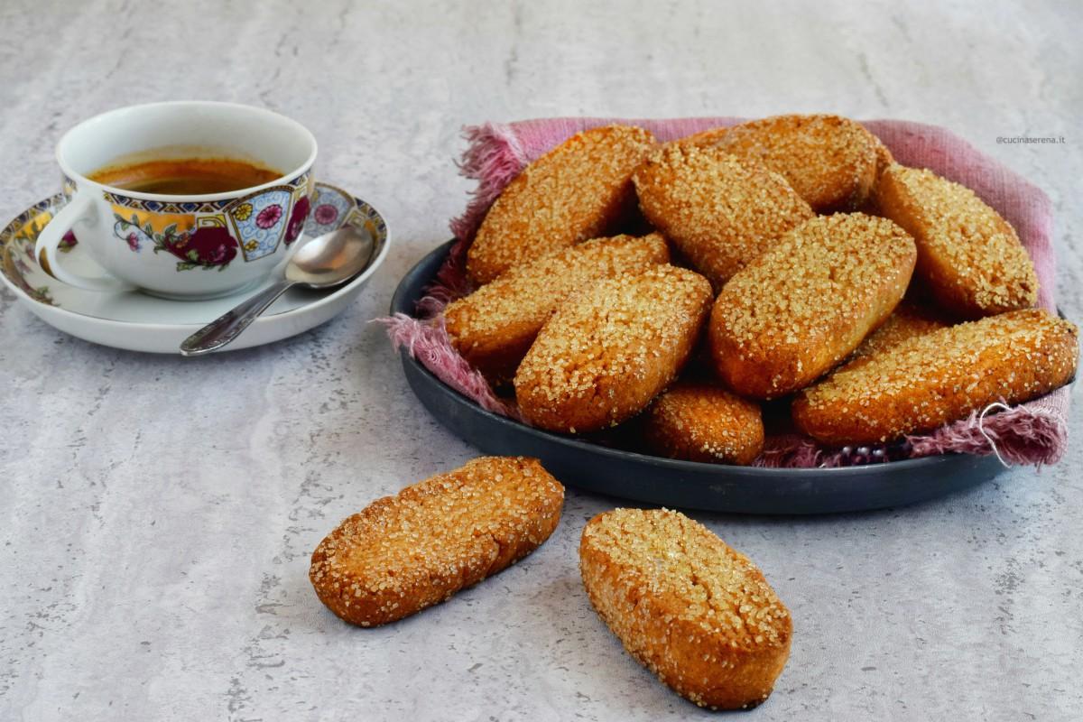 Biscotti light senza burro nè uova, nella foto presentati in una teglia tonda con un tovagliolo di lino accanto una tazzina con un caffè