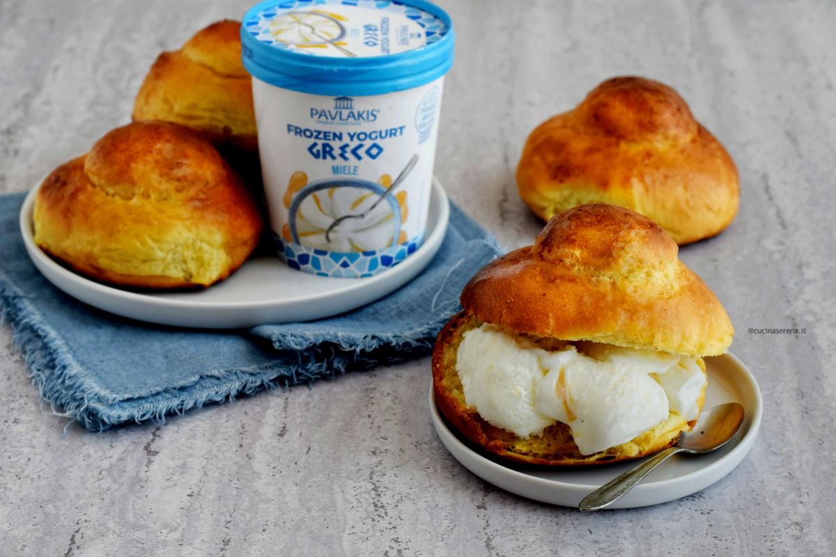 La brioche col tuppo nella foto presentata tagliata e farcita con frozen yogurt gelato, sullo sfondo altre brioche intere e  un vasetto di forzen yogurt gelato al miele Pavlakis