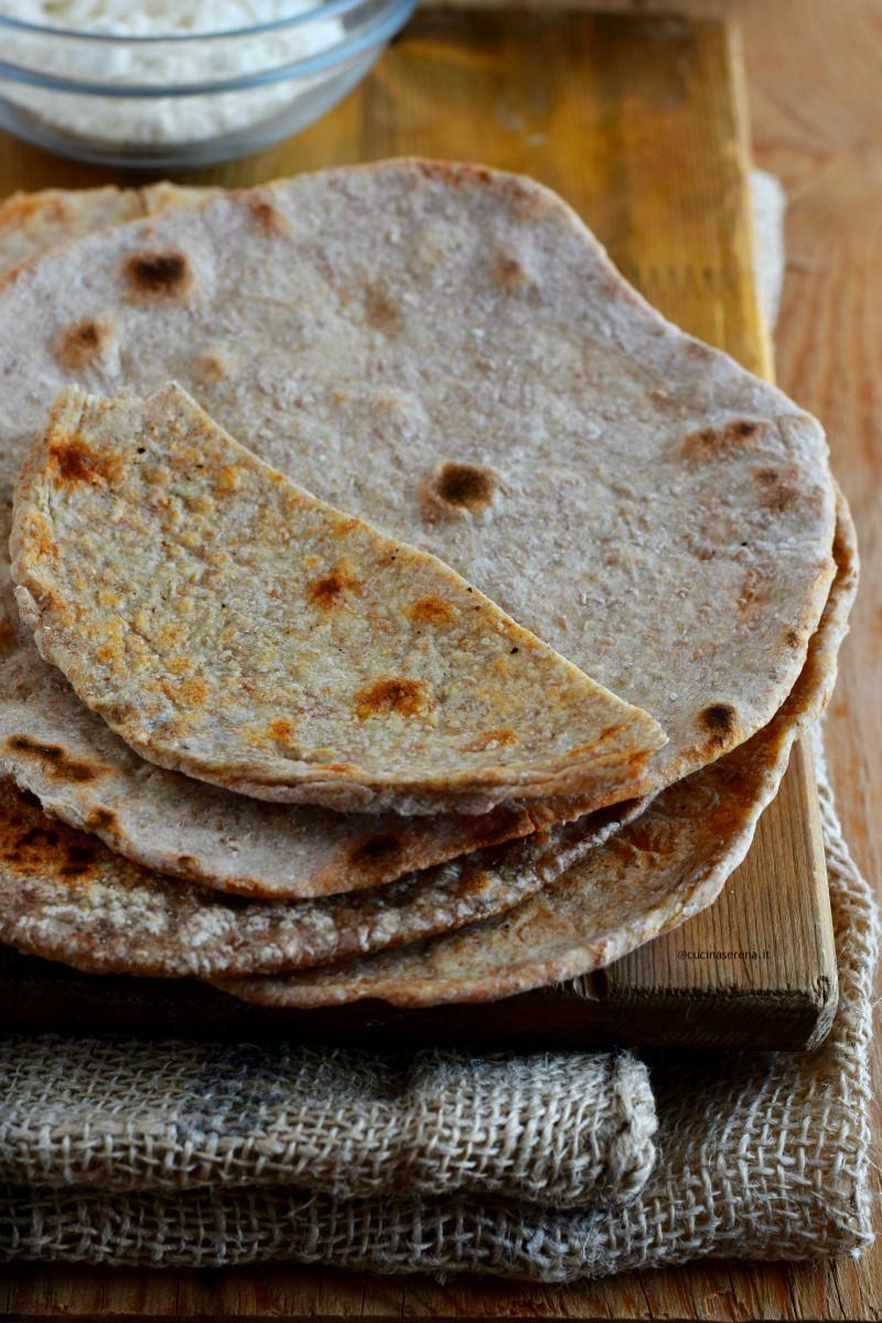 Chapati: pane indiano senza lievito fatto soltnato con farina integrale, acqua e sale dalla forma rotonda. Nella foto tre sfoglie disposte una sopra l'altra i cima un pezzetto tagliato