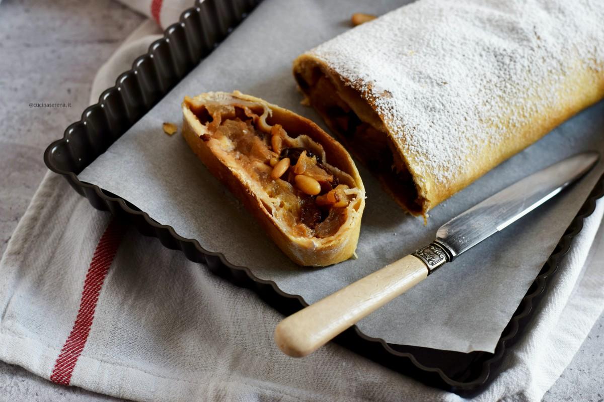 Strudel di mele nella foto una fetta tagliata adagiata su una teglia con carta forno. Dalla fetta di vedono tutti gli ingredienti che compongono lo strudel