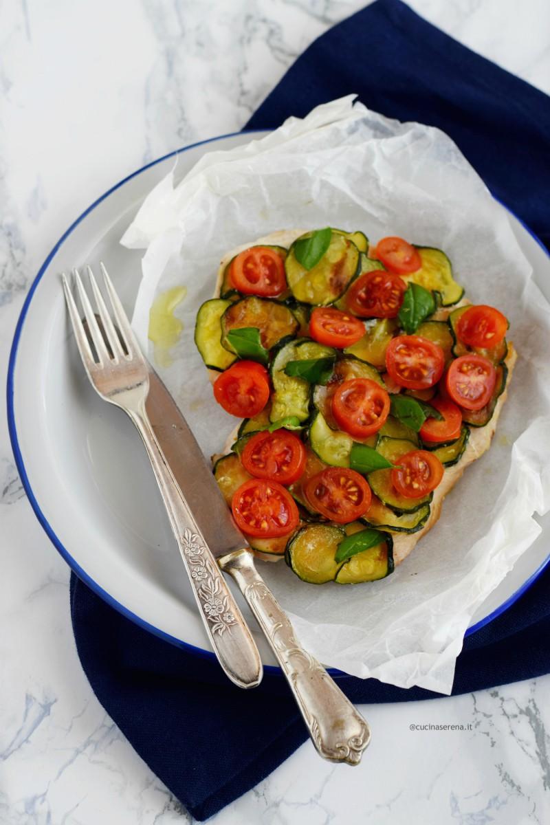 Petto di tacchino al cartoccio in padella con zucchine e pomodorini - ricetta light nella foto servito ne piatto con tutto il suo cartoccio