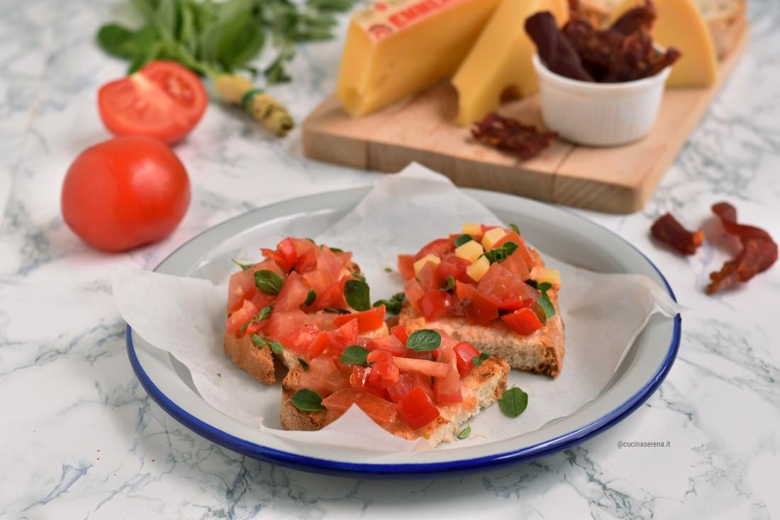 Panzanella alla romana ricetta classica, fetta di pane con pomodoro strofinato e a pezzetti condito con olio e aceto e arricchito di salvia e/o basilico