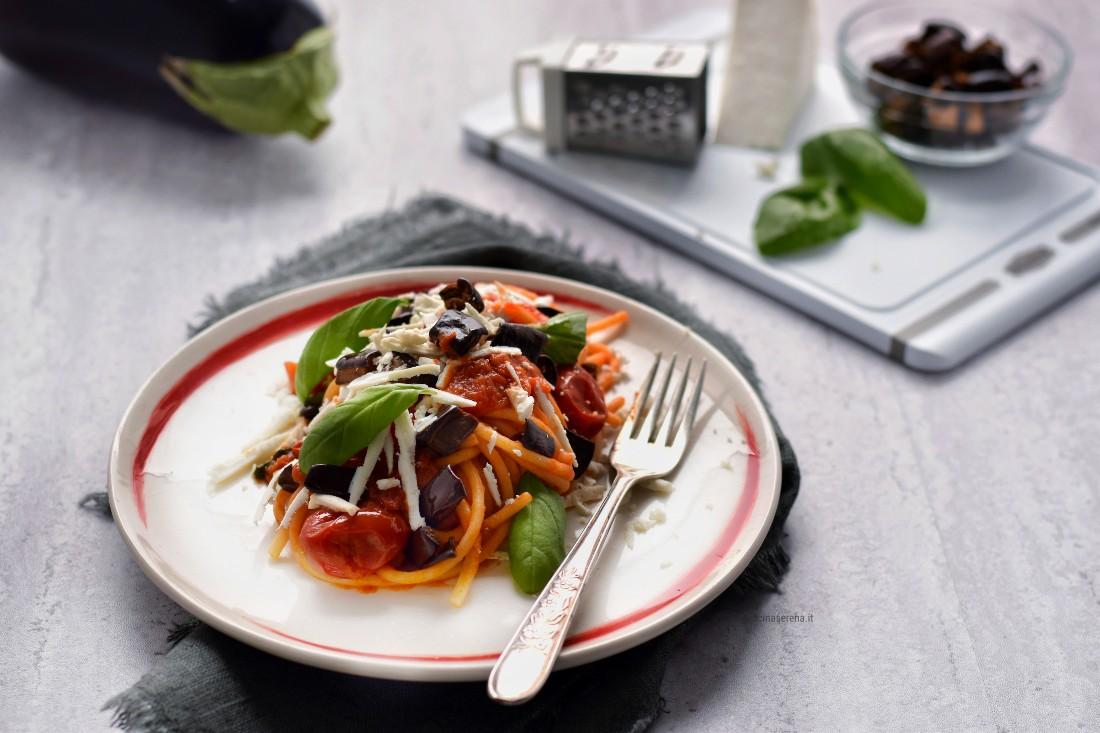 Pasta alla norma light nella foto servita nel piatto con una forchetta sul lato destro del piatto e attorno sparsi gli ingredienti della ricetta