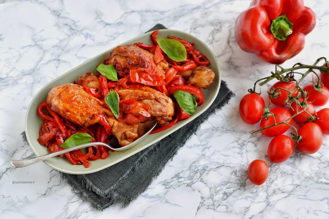 Pollo con peperoni alla romana nella foto pollo a pezzi presentato in un vassoio con peperoni rossi