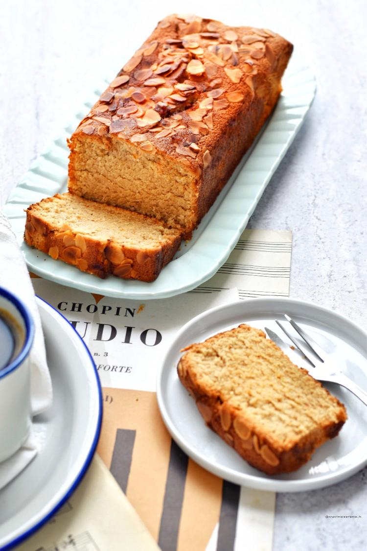 Plumcake agli allbumi senza latte e burro ricoperto di scaglie di mandorle nella foto è su un vassoio con una fetta tagliata da cui si vede la texture interna