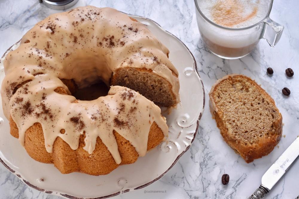 Torta al cappuccino con glassa al caffè presentata in un piatto, tagliata con una fetta accanto al piatto con il cappuccino sullo sfondo